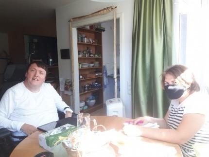 Foto: Mann im Rollstuhl, gemeinsam mit einer Frau an einem Tisch in einer Wohnung