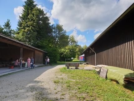 Foto, das einen kleinen Platz zeigt, der links von einer Scheune und rechts von einem Holzhaus begrenzt wird.