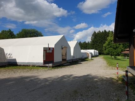 Foto, das den Zeltplatz zeigt. Im Vordergrund sieht man einen Kiesplatz im Hintergrund die Schlafzelte