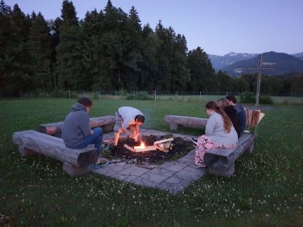 Foto, das eine Gruppe Jugendliche zeigt, die beobachten wie ein Lagerfeuer entfacht wird.