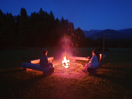 Foto, das eine Gruppe Jugendliche zeigt, die im Dunkeln um ein Lagerfeuer sitzen und in die Flammen schauen.