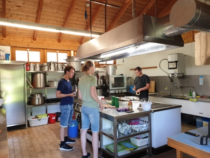 Foto, das drei Männer zeigt, die in einer großen Küche arbeiten.
