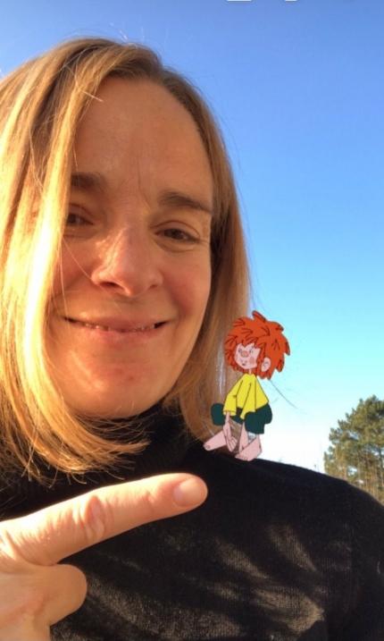 Foto: Portrait einer lächelnden Frau mit einem Zeichentrick-Pumuckl auf der Schulter
