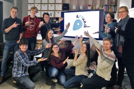 Gruppenfoto mit sechs aROund-Redakteuren, Anne, Hanna, Frederic und Erik, die auf einen Bildschrim zeigen, auf dem das aROund-Logo abgebildet ist.
