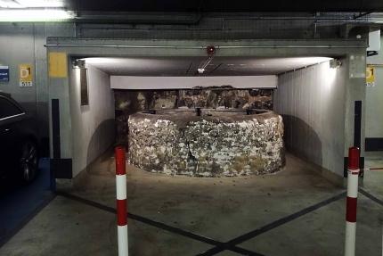 Foto einer Brunnenruine die überdacht wurde und um die ein Parkhaus herumgebaut wurde.