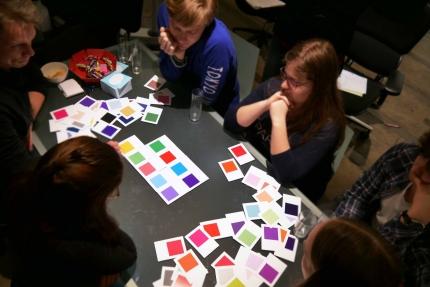 Foto: aROund-Redakteure, die um einen Tisch sitzen, auf dem viele verschiedene Farbkarten ausgelegt sind.