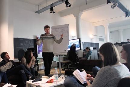 Foto: Ein junger Mann steht gestikulierend vor einem Plakat und redet mit den aROund-Redakteuren.