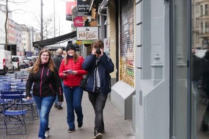 Foto von drei aROund-Redakteuren, die mit Notizblock und Fotokamera in der Stadt unterwegs sind.