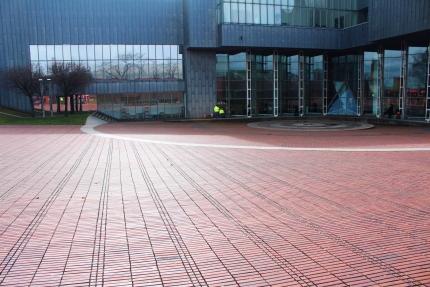 Foto zeigt einen leeren, rot gepflasterten Platz vor einem grauen Gebäude