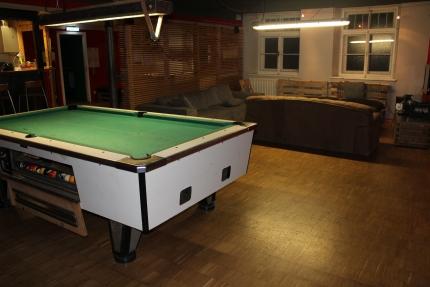 Foto eines großzügigen Raumes mit Billiardtisch und Sofa-Ecke