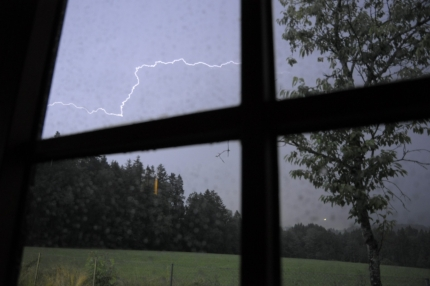 Foto aus einem Fenster, das einen Blitz zeigt, der über den Himmel zuckt.