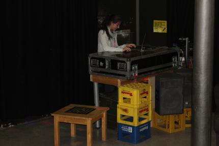 Foto einer Jugendlichen die an der DJ-Anlage eines Partyraums steht.