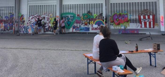 Foto: junge Leute beim Sprayern an einer Wand mit vielen Graffitis auf einem verlassenen Gelände