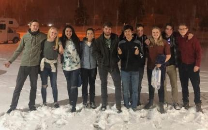 Foto: Eine Gruppe Jugendlicher (Kiannas Freunde) auf einem dick verschneiten Parkplatz