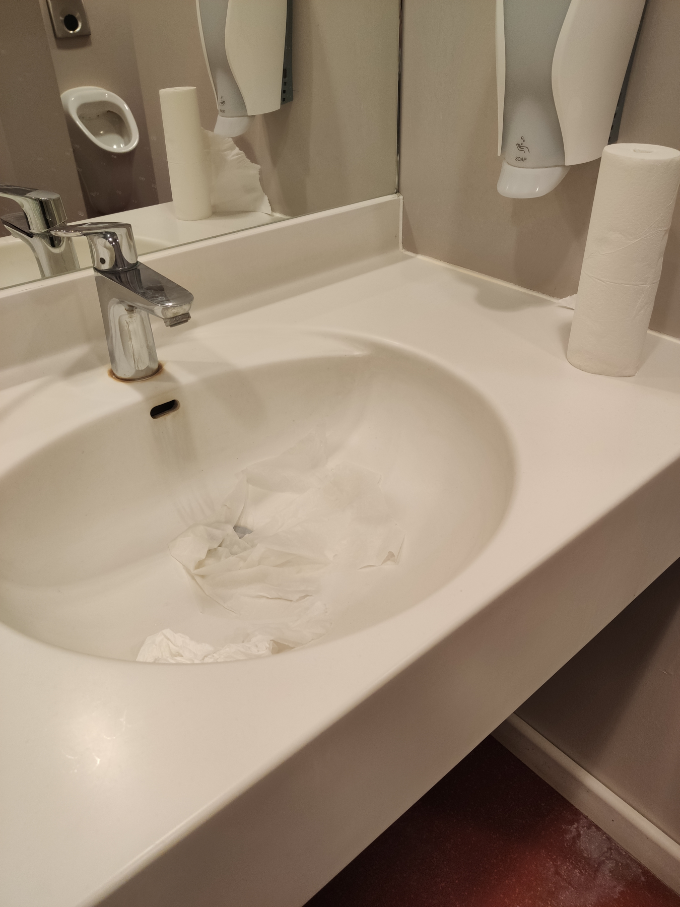 Bild eines Waschtisches, auf dem neben dem Becken eine Rolle Papiertücher steht