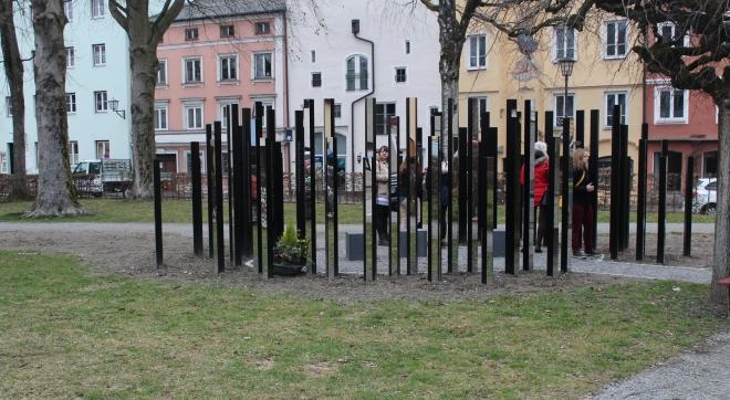 Foto: Viele schmale Stelen, die kreisförmig in einer kleinen Parkanlage vor Häuserfassaden stehen.Einige Stelen sind verspiegelt. Man erkennt Menschen, die sich die Spiegel anschauen.