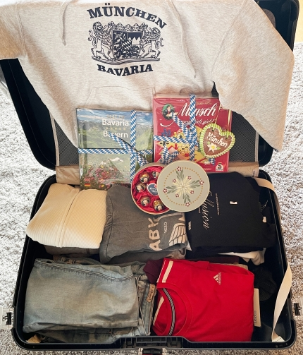 Foto: Ein offener, voll gepackter Koffer mit Kleidung und bayerischen Mitbringseln