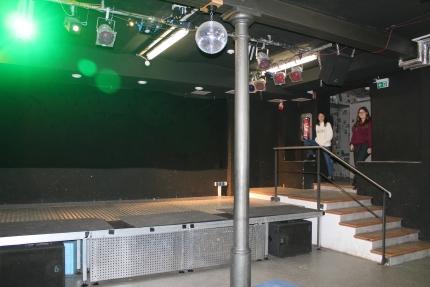 Foto zeigt einen fast leeren, dunklen Partyraum mit Bühne und Tanzfläche.