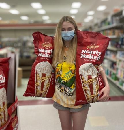 Foto: Anna im Supermarkt mit zwei gigantisch großen Popcorn Tüten