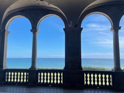 Foto: Torbögen an einer Terrasse und dahinter ein Blick auf den blauen Ozean