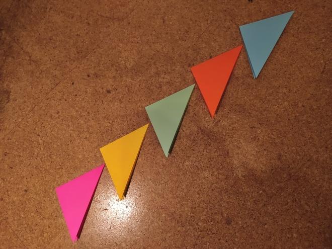Foto: Fünf doppelt zu Dreiecken gefaltete Bastelpapiere