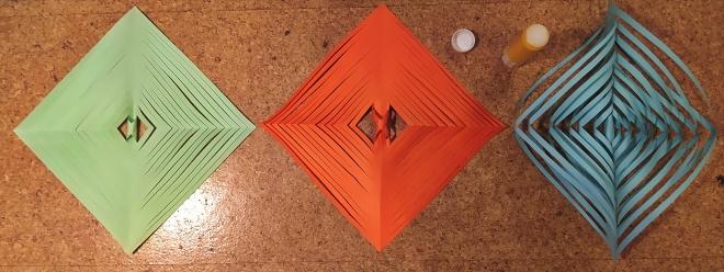 Foto: Drei nebeneinanderliegende aufgefaltete Papiere und ein Klebestift