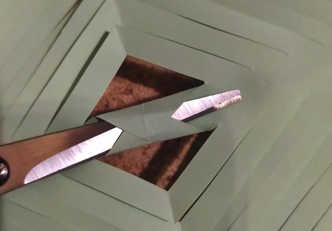 Foto: Detailaufnahme: mit einer Schere die Mitte des Papiers zusammenkleben
