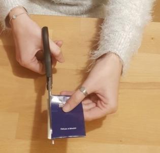 Foto: Hände schneidet mit einer Schere den Rand einer Teebeutel-Umverpackung ab
