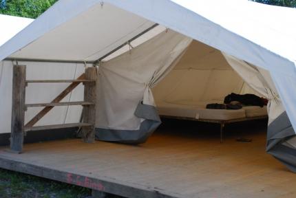 Foto, das den Innenraum unserer Schlafzelte zeigt. Im Vorderen Bereich hat man Platz seine Sachen zu verstauen im Hinteren Bereich sieht man viele Matratzen auf Bettgestellen nebeneinander