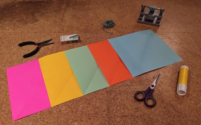 Foto: Bereitsgelegtes Bastelmaterial: 5 bunte Papiere, Schere, Kleber, Locher, Tackernadeln, Zange