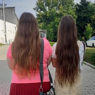 Foto: Zwei junge Frauen mit langen, offenen Haaren von hinten